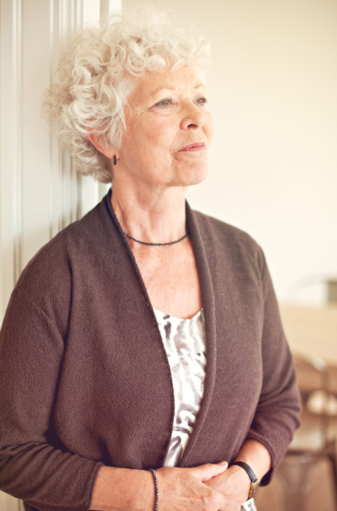 Senior woman with white hair looking into the distance with a bit of a smile