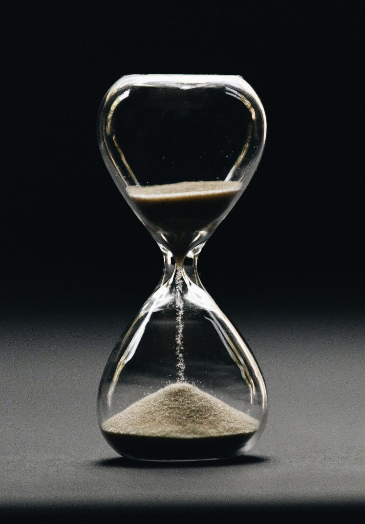 Clear hourglass slowing seeping grains of sand.