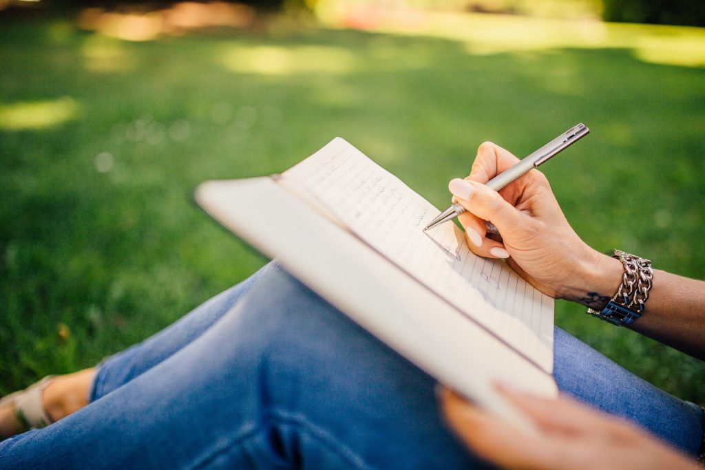 Woman sitting on grass writing in notebook.