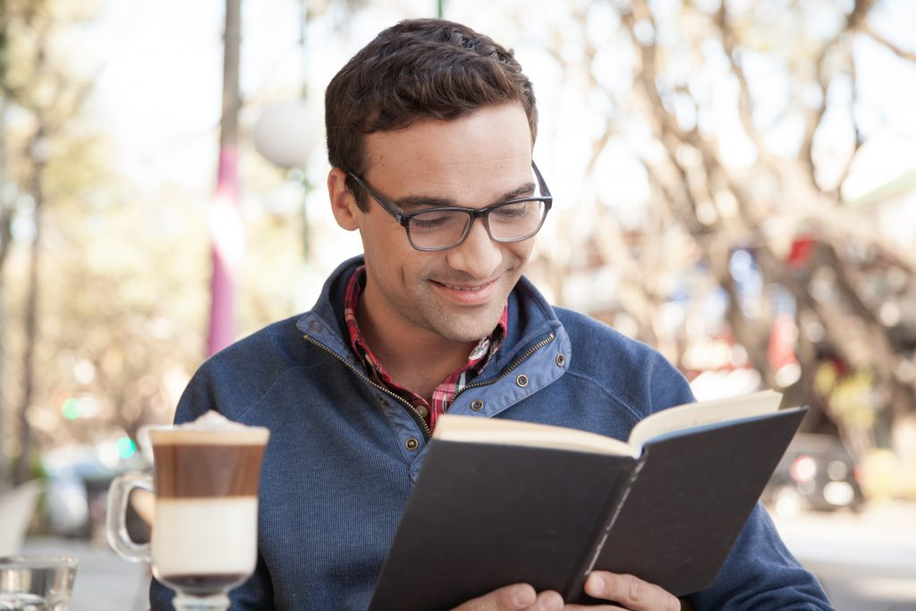 Person sitting outdoors smiles as he reads a book.
