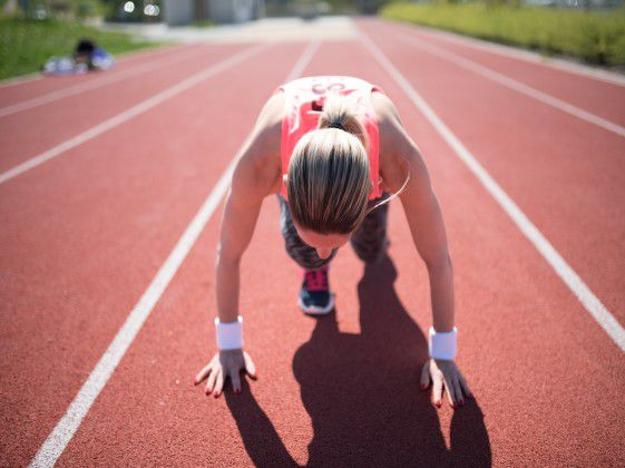 Young woman in starting position stance getting ready to run race on a track.
