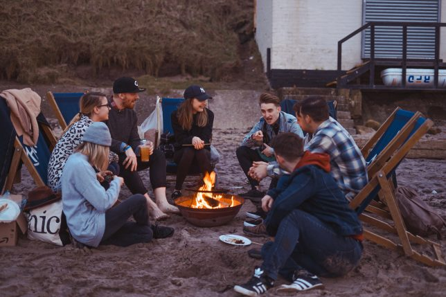 People in their twenties sitting around a fire pit on a beach.