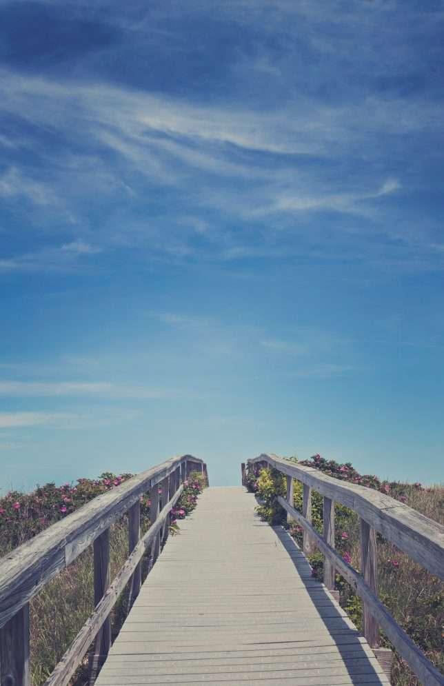 Wood bridge with rails under a beautiful blue sky.